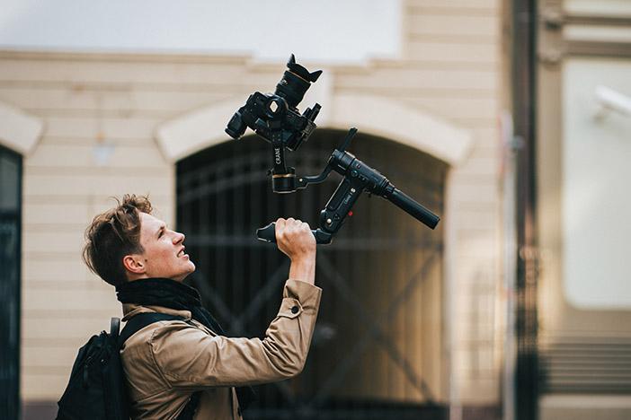 Man holding Zhiyun Crane 3S with camera mounted