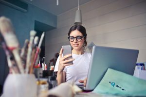 Live-Streaming-101-woman-in-white-t-shirt-holding-smartphone-in-front-of-laptop