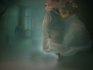 Pregnant woman in dress underwater